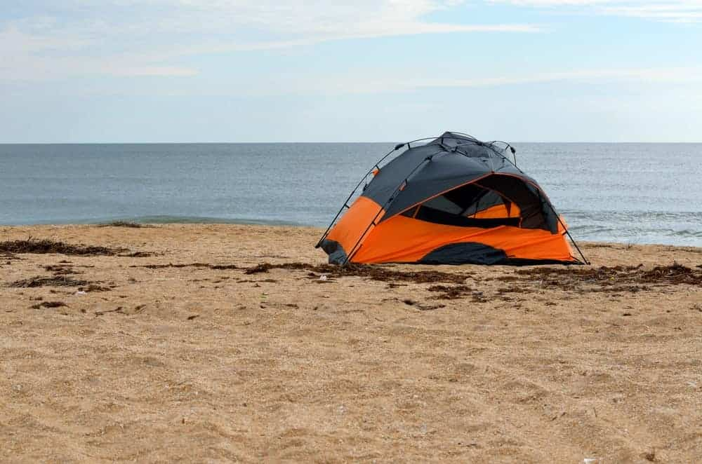 A tent pitched along a beachshore.