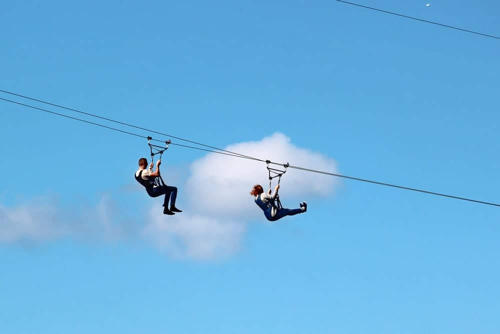 Two person ziplining against a backdrop of a clear sky.