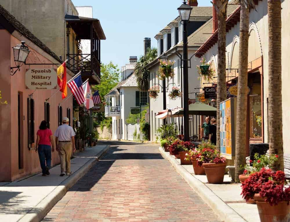 A couple walking on the sidestreet of the Historic District in St. Augustine, FL.