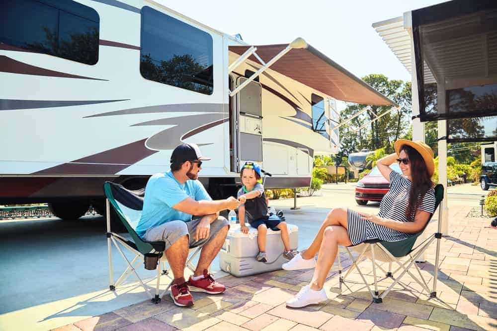 A family of three sits outside an RV.