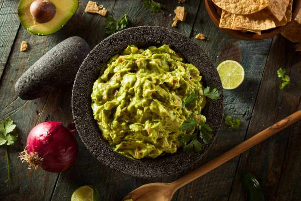 Guacamole on a molcajete surrounded by ingredients.
