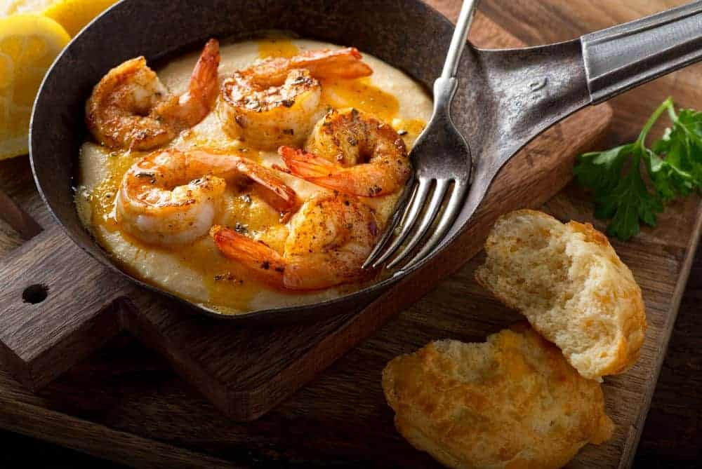 A shrimp dish in a pan with fork placed on wooden chopping boards and cut bread on the side.