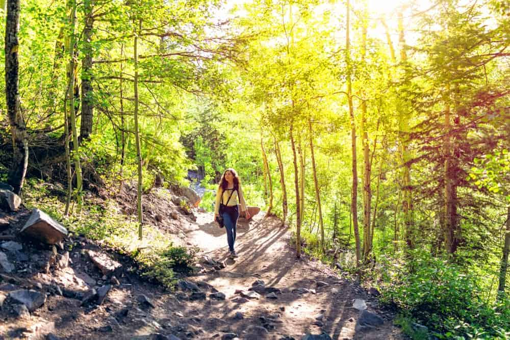 A woman walking in one of the hiking trails of Woodland Park, CO.