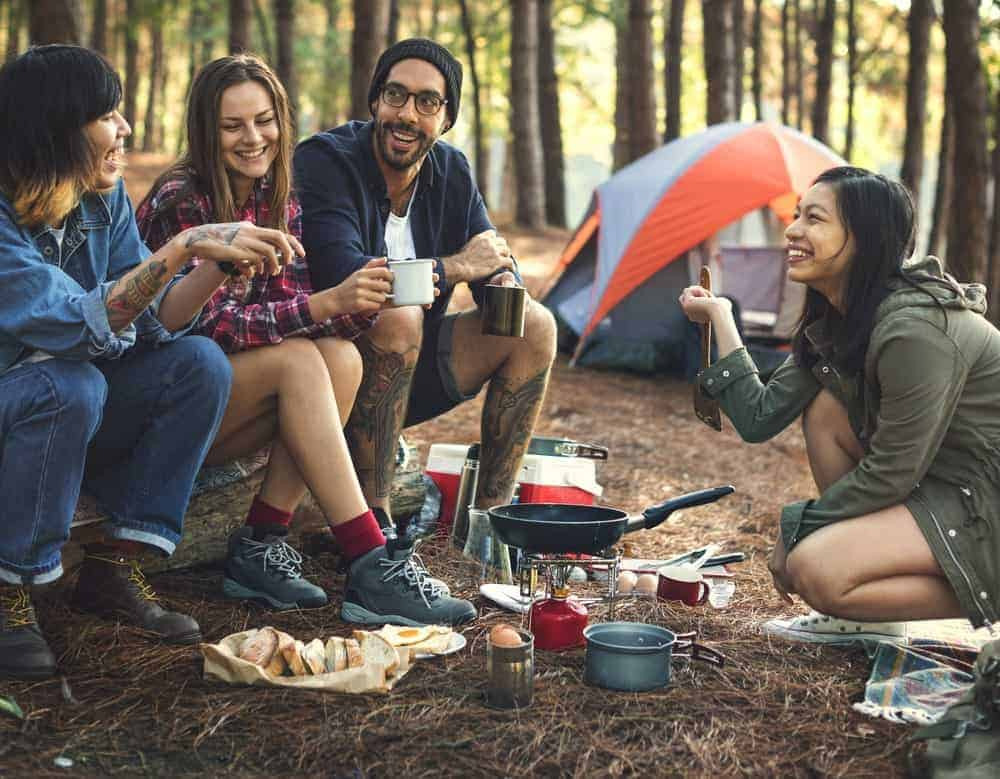 A group of friends cooking food outdoor on a camping trip.