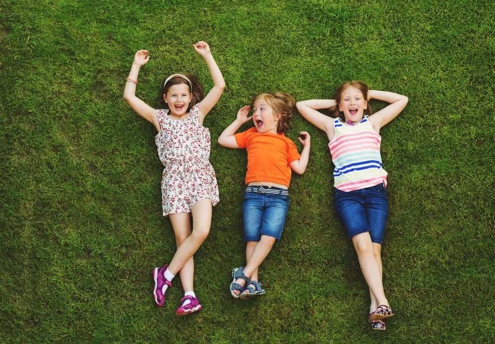 Three kids enjoying the grass lawn of the Memorial Park.