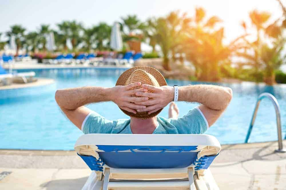 Back view of a man relaxing beside a pool.