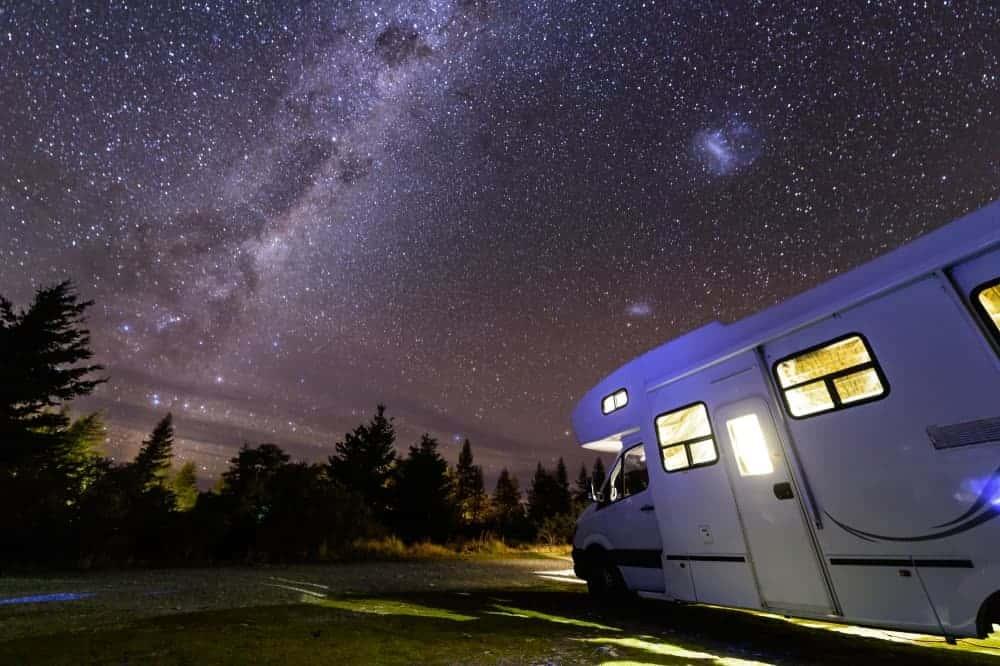 An RV parked under a starry night sky.