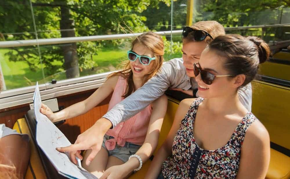 A young trio of friends looking at a map while on a ride.