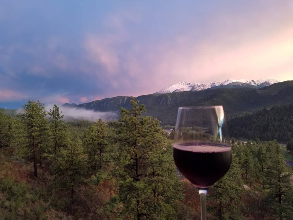A glass of wine overlooking the scenery of Woodland Park.