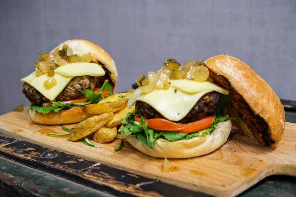 A couple of beef cheeseburgers and fries on a wooden chopping board.