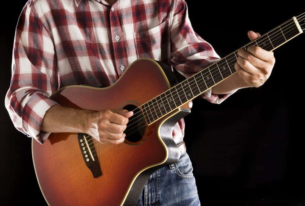 A man in checkered shirt plays a guitar.