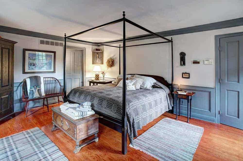 A colonial-style master suite with a four-poster bed, wooden furniture, and area rugs on hardwood flooring.