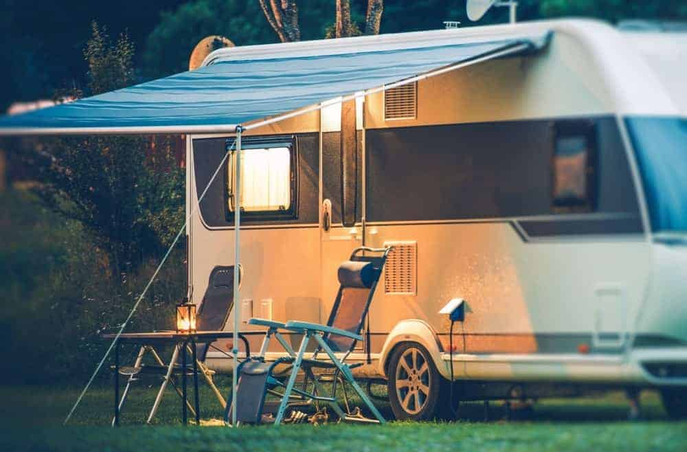 An RV parked with an extended tarp roofing and a foldable table flanked by foldable chairs.