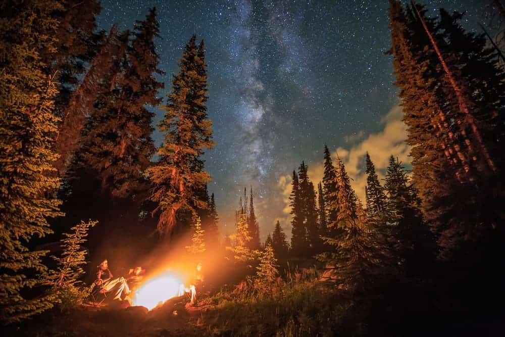 A family stargazing while camping.