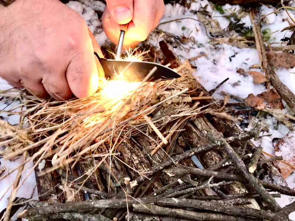 A close look at a person building a fire with tools.