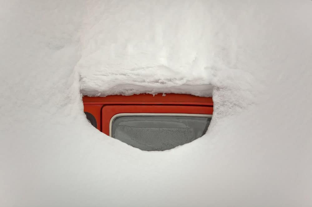 Window of a red car completely buried in snow.