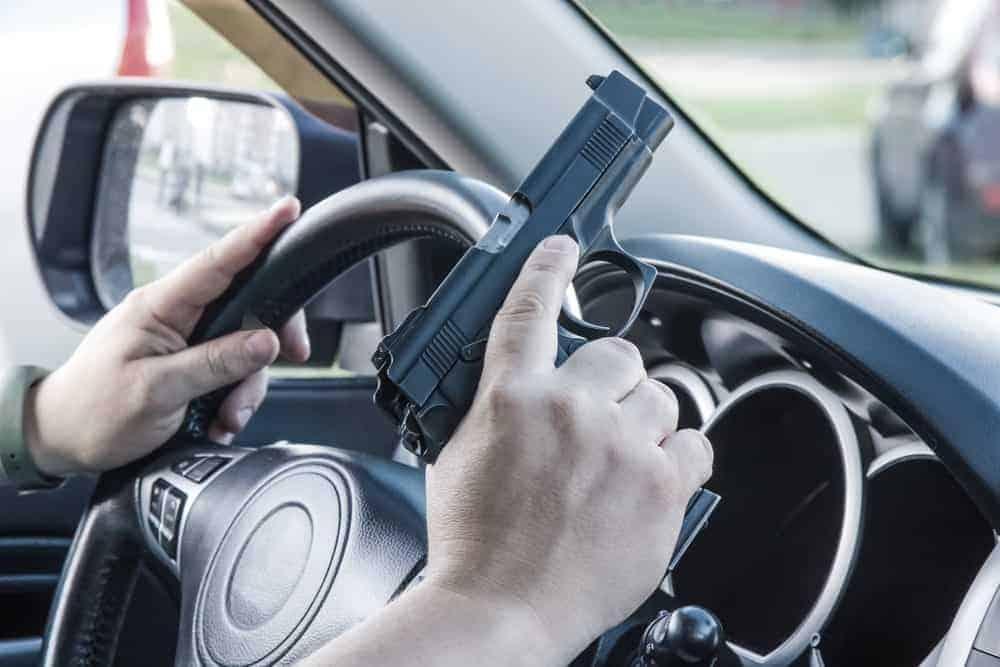 A driver holding a gun.
