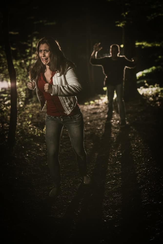 Frightened woman escaping from a man in the woods.