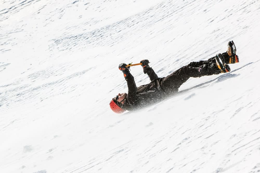 A climber falls on a snow slope.