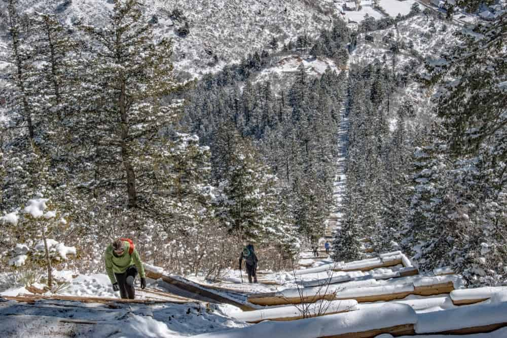 Hikers hike at a snowy-capped mountain trail among pine trees.