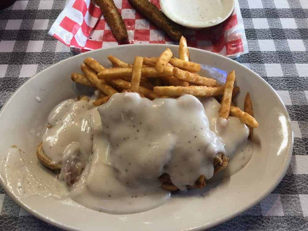 A dish of fries and chicken stake topped with white gravy.