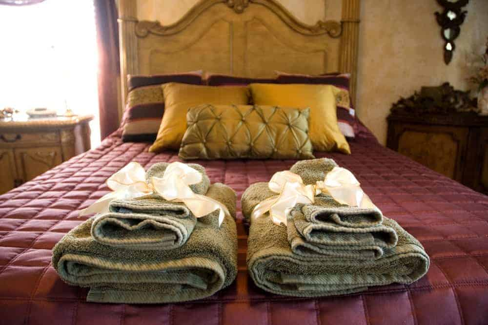 A double bed with folded towels for guests at The Katy House.