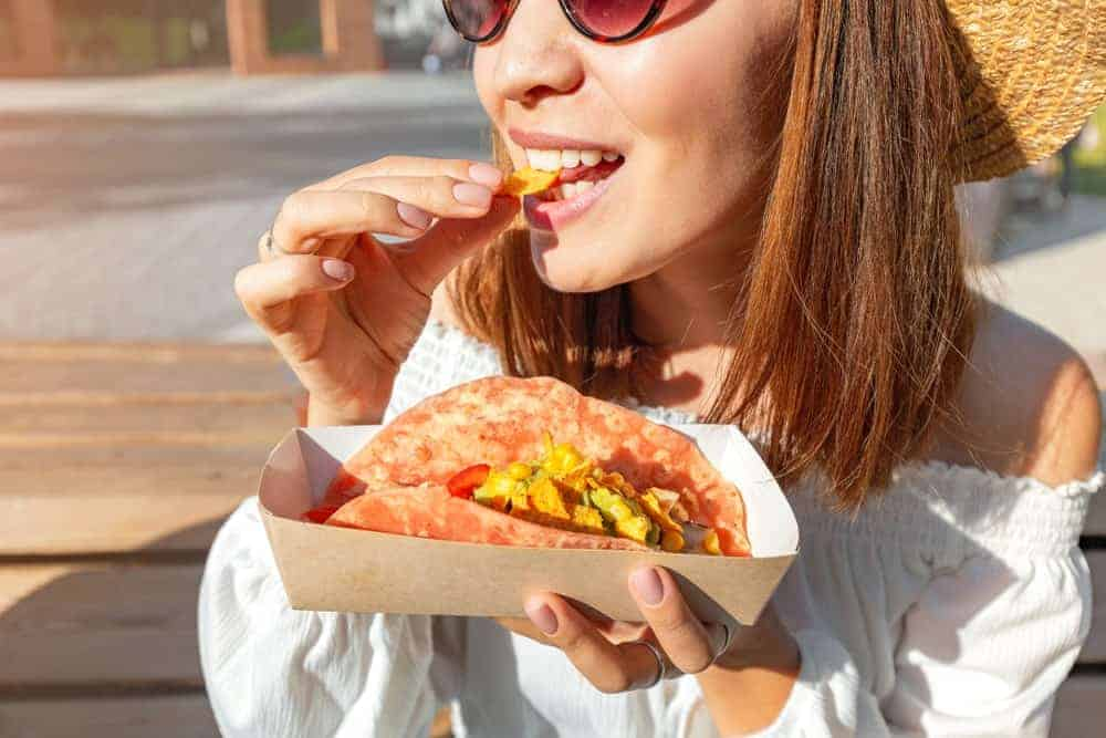 A woman wearing a hat and shades and eating tacos.