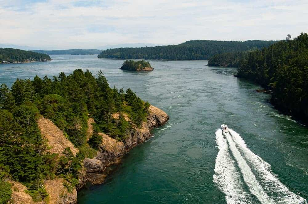 An aerial view of a speed boating cruising through small islands.