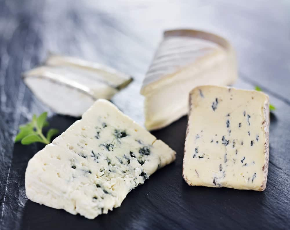 Assorted gourmet cheese on a dark wooden surface.