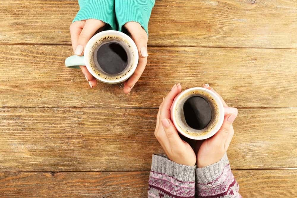 Top view of hands holding cups of coffee from opposite sides of the table.