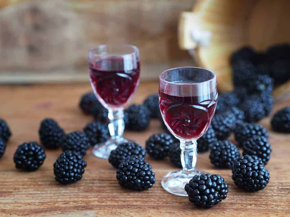 Blackberry liqueur in a pair of crystal wine glasses surrounded by blackberries.