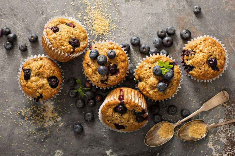 Blueberry cupcakes surrounded by blueberries and a pair of vintage spoons.