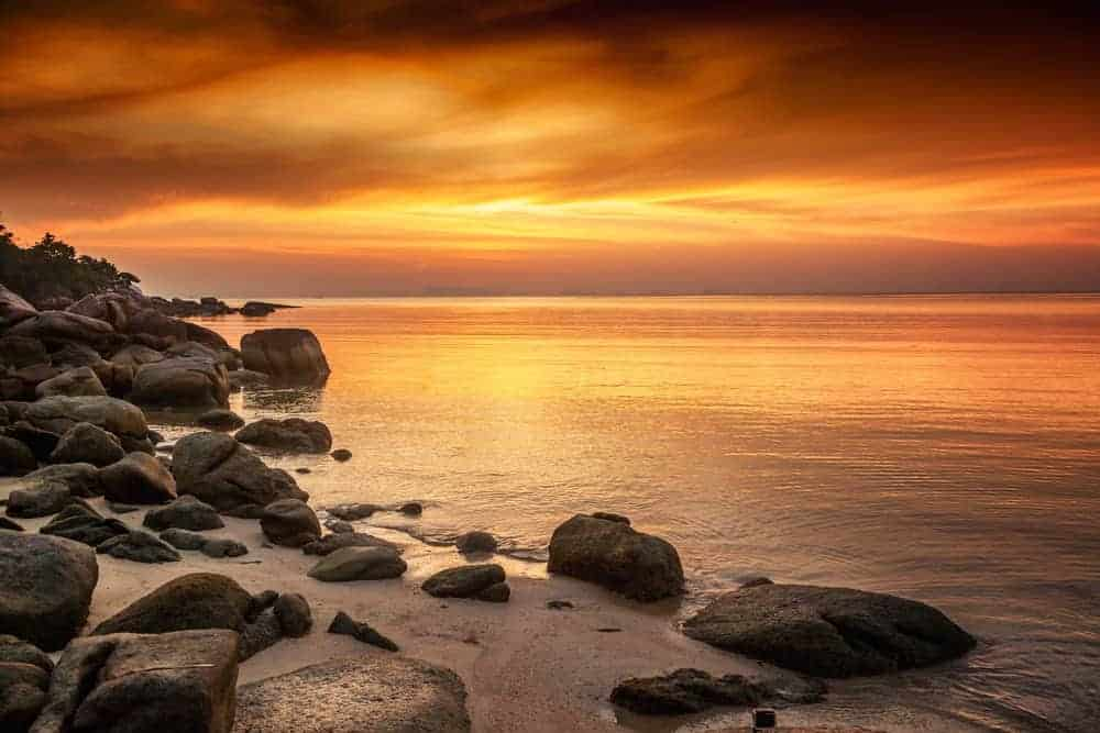 A view of a rocky beach at sunset.