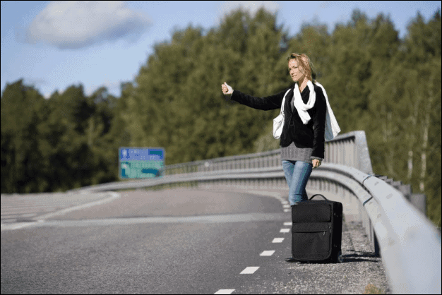 Young Hitchhiking Woman with a Travel Bag.
