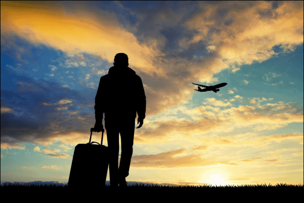 Silhouette of a Man Walking with a Travel Suitcase.