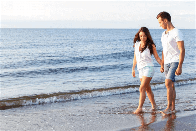 Young Couple Holding Hands at the beach.