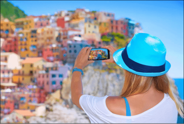 Woman Taking a Picture of Colorful Buildings.