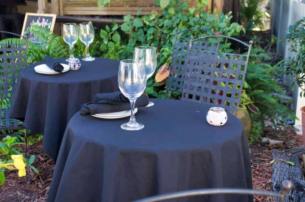 Wineglasses on tables wrapped with dark tablecloths in al fresco style dining.