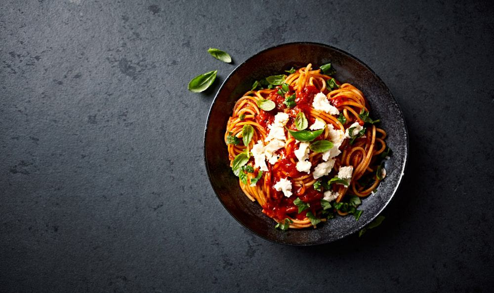 A bowl of spaghetti with tomato sauce, mozzarella, and basil.