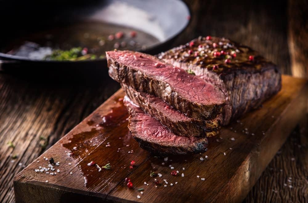 Medium beef rib eye steak slices on a chopping board.