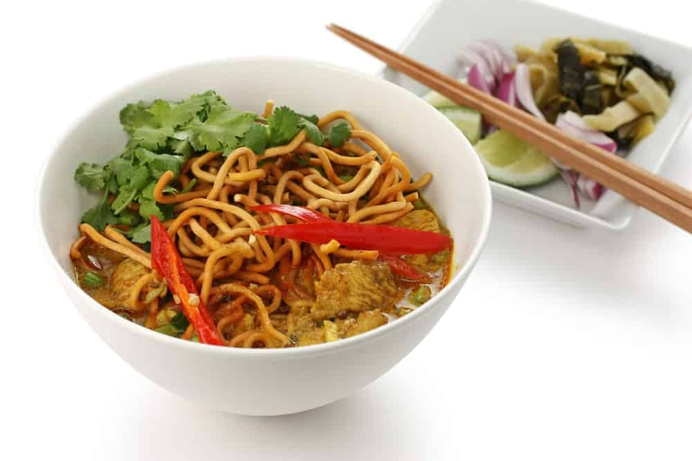 A bowl of Khao soi with toppings.