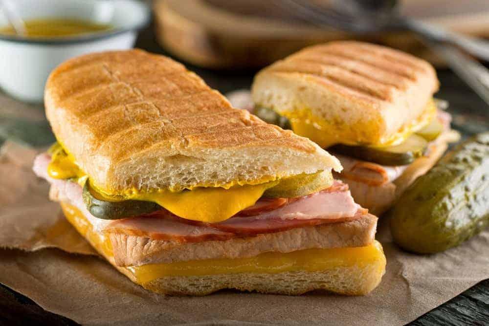 A pair of Cuban sandwiches beside a pickle.