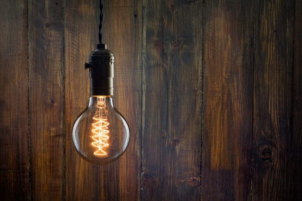 An incandescent Edison type bulb against a wooden wall.