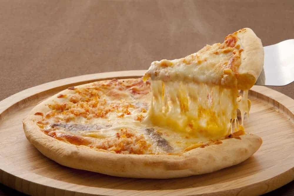Getting a slice of cheesy pizza.