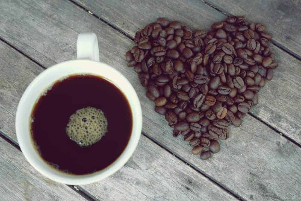 Top view of a cup of coffee beside black beans that form a heart shape.