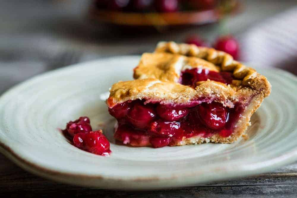 A slice of homemade cherry pie on a plate.