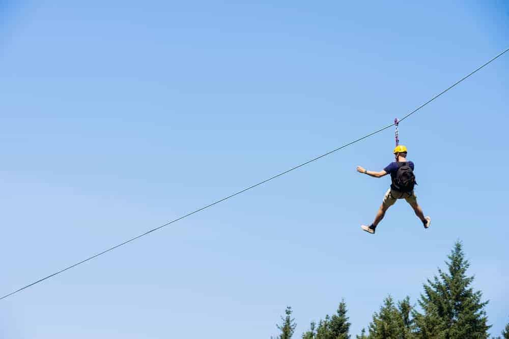 A man ziplines above treetops.