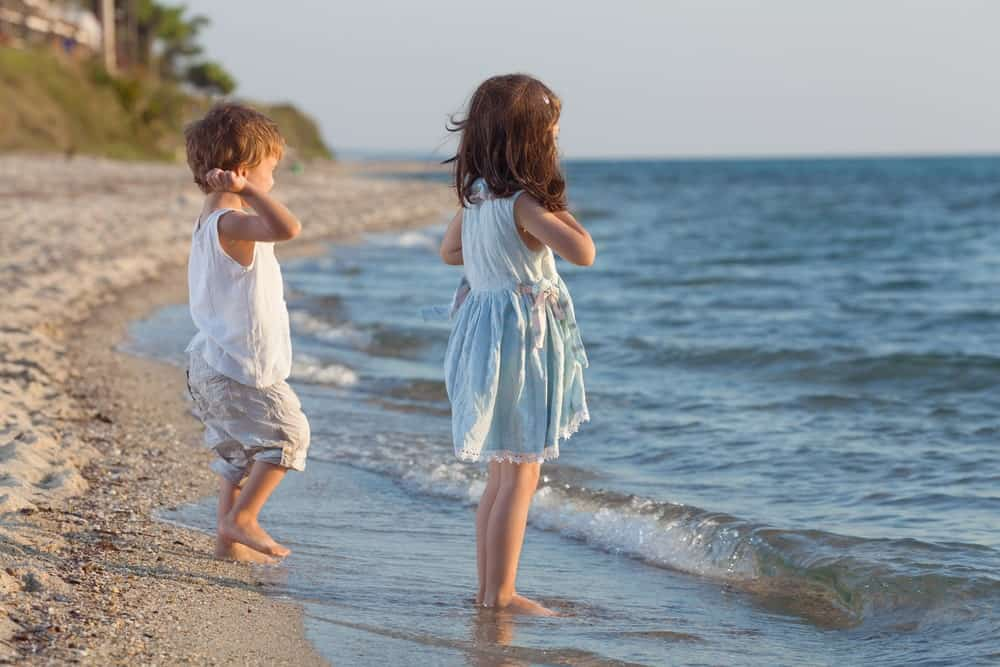 Two kids playing on the beach throwing rocks.