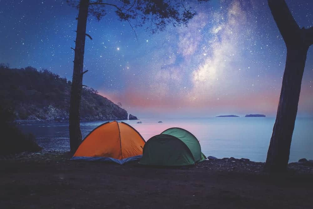 Tent camping on shore at night.