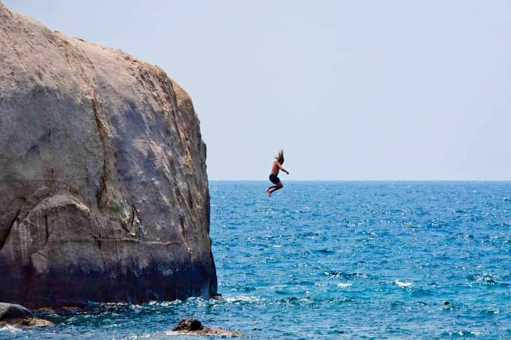 A man jumping off cliff into the sea.